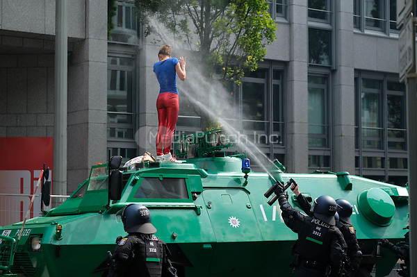 Two police officers in riot gear spray a woman with pepper spray after she had climbed onto an armoured police vehicle during demonstrations against the G20 summit in Hamburg, Germany, 7 July 2017. The summit, a meeting of the governments of the twenty largest world economies, begins on the 7 July and concludes on the 8 July. Photo: Boris Roessler/dpa /MediaPunch ***FOR USA ONLY***