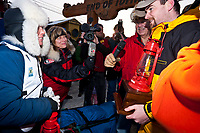Rookie musher Celeste Davis receives her red lantern award from Wells Fargo at the finish line in Nome during the 2010 Iditarod