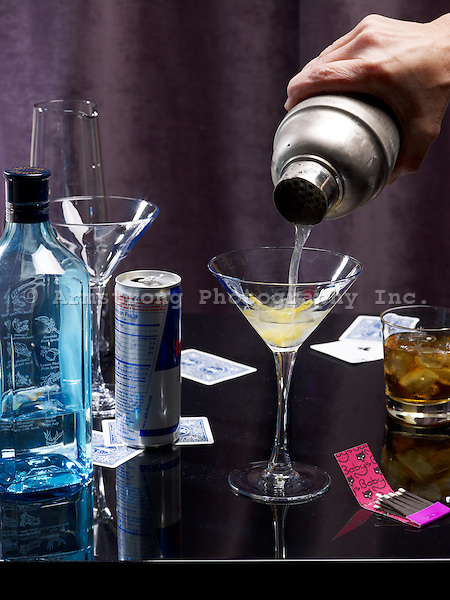 Pouring a martini from a cocktail shaker. Pictured with bottle of gin, Red Bull can, whiskey cocktail, playing cards, matchbook, and empty glassware.