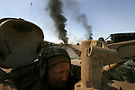 A tank crewmen attached to 2nd Battalion 1st Marines peers out from the safety of his tank to survey his surroundings as the Marines continue with Operation Steel Curtain in Ubaydi, Iraq on Tues. Nov. 14, 2005.