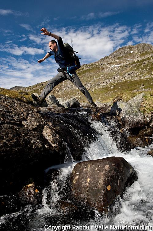 Mann hopper over bekk. ---- Man jumping smal creek.