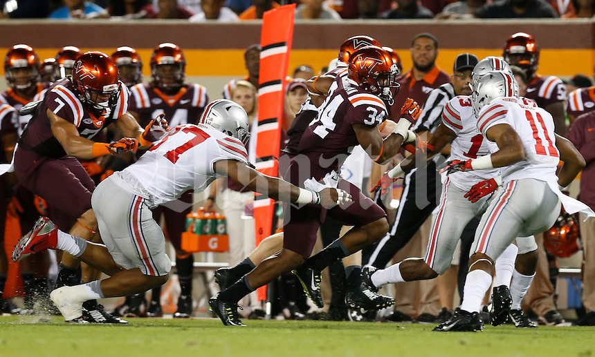 Ohio State Buckeyes linebacker Joshua Perry (37) teams up with cornerback Eli Apple (13) and safety Vonn Bell (11) to tackle Virginia Tech Hokies running back Travon McMillian (34) during Monday's NCAA Division I football game in Blacksburg, Va., on September 7, 2015. The Ohio State won the game 42-24. (Dispatch Photo by Barbara J. Perenic)