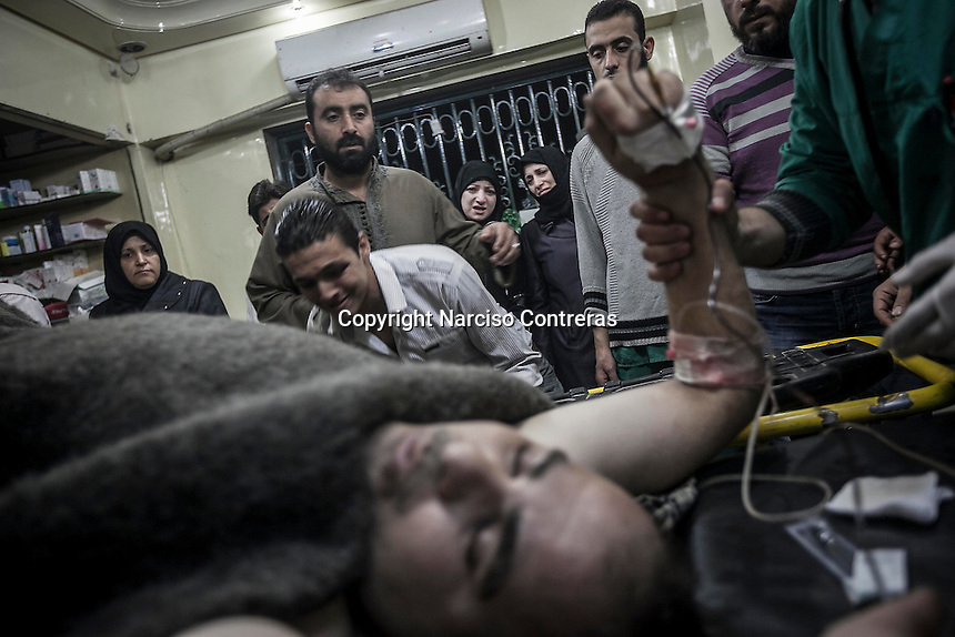 In this Saturday, Oct. 27, 2012 photo. Relatives of a Syrian civilian sob as he lies on a trolley of one hospital in Tarik Al-Bab after he has arrived wounded by one sniper shoot at his back, Aleppo City. (AP Photo/Narciso Contreras).