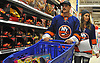 "Ryan Pulock of the New York Islanders and Paige Friesen fill their cart with presents at Toys ""R"" Us in Carle Place during the team's holiday shopping for children in hospitals on Thursday, Nov. 30, 2017. The gifts will be hand-delivered to children in eight local hospitals by the players on Monday, Dec. 18."