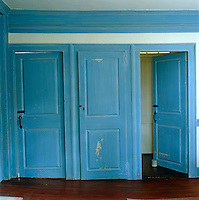 In the kitchen three doors have been painted the same distressed blue contrasting with the deep reddish-brown of the aged floorboards