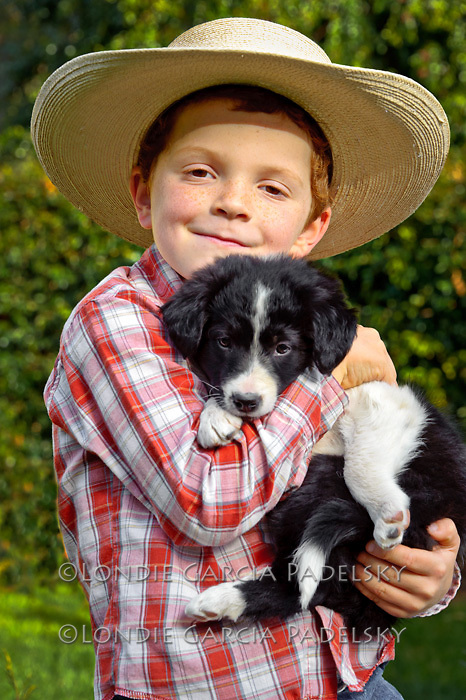 Little cowpoke and border collie puppy.