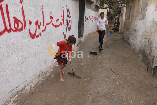 A Palestinian girl cleans on an alley on a raining day at al-Shati refugee camp, the third largest in the Palestinian Territories, in Gaza City on October 30, 2013. Photo by Mohammed Asad