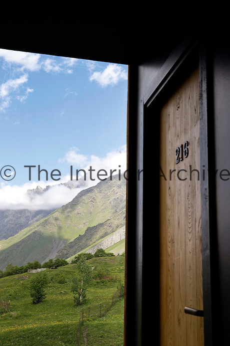 An open bedroom door at Hotel Rooms reveals the spectacular mountain scenery which is its backdrop