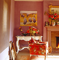 Sunlight pours into this cosy sitting room converting the ordinarily dark purple walls to a lilac hue