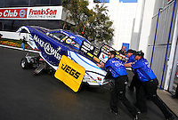 Feb 7, 2014; Pomona, CA, USA; crew members push the car of NHRA funny car driver Tommy Johnson Jr out of the staging lanes out onto the track during qualifying for the Winternationals at Auto Club Raceway at Pomona. Mandatory Credit: Mark J. Rebilas-
