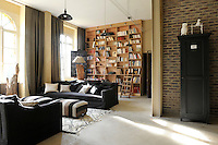 In the living room industrial brick walls and steel beams are softened by linen-covered sofas and a wool rug