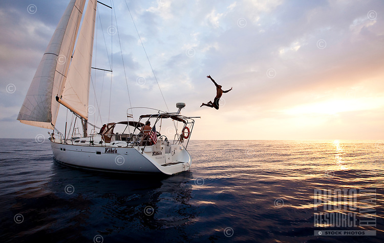 Young man jumping off a sailboat on the west side of Oahu