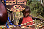 Africa, Kenya, Maasai Mara. Young Maasai boy peeks out at boma market.