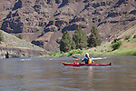 Howie Wallace paddles the lower John Day River Canyon in a Necky Looksha Sport kayak.  Trees are junipers.  Rock is basalt.
