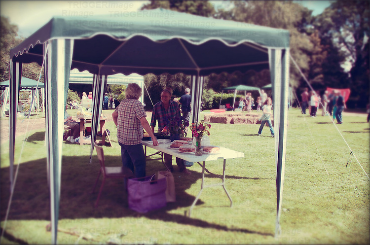 People enjoying a small summer fete in the village of Brome & Oakley in Suffolk, England.