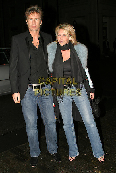 LEE CHAPMAN & LESLIE ASH.The Saatchi Gallery's first anniversary party at County Hall which coincides with the launch of new exhibition New Blood.23 March 2004.full length, full-length, denim jeans.www.capitalpictures.com.sales@capitalpictures.com.© Capital Pictures.