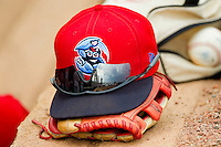 A Lakewood Blue Claws cap sits on a glove in the visitors dugout at L.P. Frans Stadium on June 5, 2011 in Hickory, North Carolina.   Photo by Brian Westerholt / Four Seam Images
