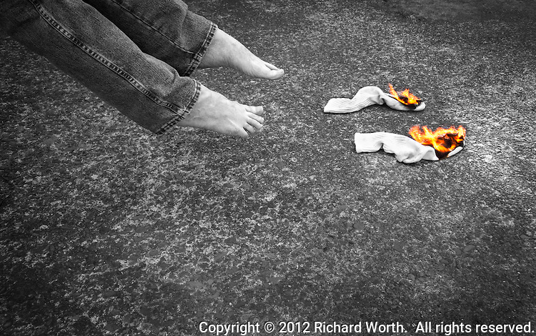 Two socks burning with two bare feet inches away.  Flames in color while the rest of the image is in black and white.