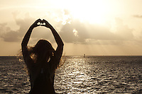 Young girl creating a hear shape at sunrise