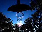 Basketball hoop in late afternoon sun.
