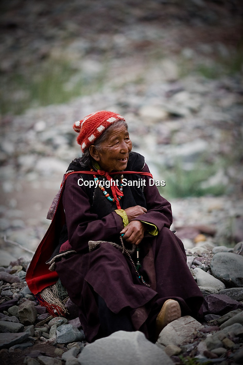 """79 year old, Tsering Angmo is a local villager and is seen waiting for His Holiness the Twelfth Gyalwang Drukpa, the head of the Drukpa Lineage to arrive in the outskirts of Hemis in Shwang. """"Walking On The World's Rooftop"""" Pad Yatra from Manali to Ladakh, of 400kms was focused at raising awareness awareness of His Holiness' charitable projects including education , environment and cultural preservation of tribal people from the area. Accompanied on the Yatra by large numbers of Buddhist monks, nuns, foreigners and local villagers. The culmination of the Pad Yatra coincides with the colourful age-old Hemis festival in Leh, Ladakh, India."""