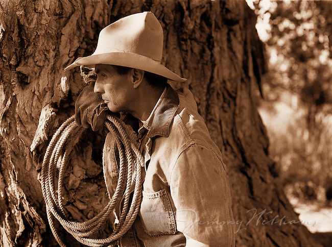 A cowboy lens against a tree, holding a whip in his hand and looking away from the camera