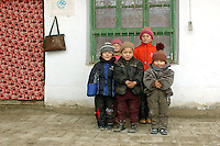 A group of Uyghur children pose for a photograph in a small town in Kuche County along the middle rout of the ancient Silk Road in Xinjiang, China. Uyghurs live mostly to the south of the Tien Sien mountains in the districts of Hotan, Kashgar, Turfan, Aksu and Korla, where they occupy oasis land on the edge of the Taklamakan Desert and Tarim Basin.