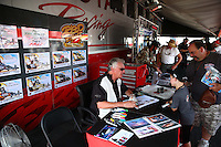 May 31, 2013; Englishtown, NJ, USA: NHRA artist Kenny Youngblood signs some of his work for fans during qualifying for the Summer Nationals at Raceway Park. Mandatory Credit: Mark J. Rebilas-
