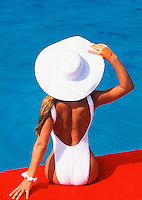 Young woman in white swimsuit and large sun hat on orange float