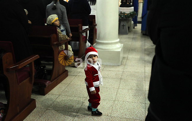 A Palestinian boy dressed as Santa Claus attends a mass ahead of Christmas at Der Latin church in Gaza City on December 18, 2016. Photo by Ashraf Amra