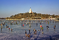 China. Beijing.  Skaters on frozen lake in Beihai Park. Jade Island and the White Dagoba..