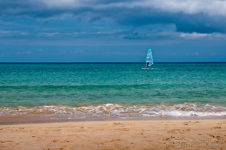Windsurfer in the water, in Fuerteventura, Canary Islands. <br /> The light blue of the sea contrasts with the dark clouds above. <br /> Image made near Costa Calma, on the east coast of Fuerteventura.