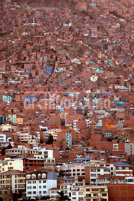 A cluster of houses and building over the lap of a mountain enclosing La Paz , the capital city of Bolivia. From an urbanologist point of view the city is quite a disorder.