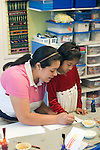 Berkeley CA Berkeley CA  Latina teacher and student working on art projects at bilingual Spanish-English preschool