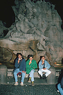 "April 27, 1990, Rome, Italy. Photographing for the book ""One day in the life of Italy"", an exploration of Rome. The end of the day. After dinner, young men enjoy traditional ice-cream,  on the city fountain."