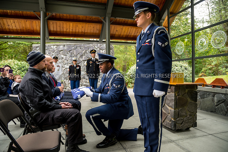 9/30/2016-- Tahoma National Cemetery, Kent, WA, USA<br /> <br /> Here: James Sosik, from the King County Medical Examiner&rsquo;s Office (seated wearing cap), volunteers to accept a flag on behalf of deceased veteran Ricky Fesler, in a commitment shelter at the Tahoma National Cemetery.<br /> <br /> James Lindley, 34, an undertaker and US Marine Corp Veteran, works at the Columbia Funeral Home in Seattle, Washington and has taken it upon himself to process the remains of indigent veterans and ensure their remains are placed in Tahoma National Cemetery in nearby Kent, WASH. The veterans are given full military funerals with active service members as well as volunteers who stand-in for unavailable next-of-kin, accepting the folded flags provided by the Veterans Administration.<br /> <br /> On this day, with the help of Mr. Lindley, the remains of 4 veterans were interred at the Tahoma National Cemetery: <br /> <br /> Richard Fesler, born 1951, died 2014. US Army Veteran<br /> Rocky Stallone, born 1951, died 2014. Marine Corps veteran<br /> Russell Ristow, born 1944, died 2014. US Army veteran.<br /> Wayne Roberts, Born 1937, died 2014. US Navy veteran.<br /> <br /> <br /> Credit: Stuart Isett for The Wall Street Journal. <br /> VETBODIES<br /> <br /> &copy;2016 Stuart Isett. All rights reserved.