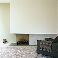 An Italian contemporary armchair in front of a basalt hearth in the living room