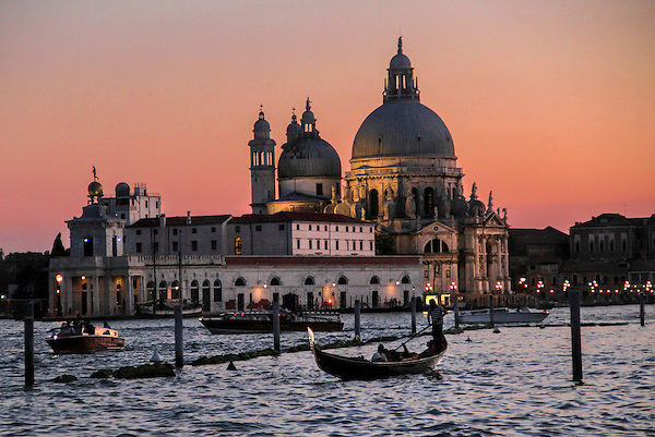 Gondolier on the Grand Canal at sunset, Venice, Italy.