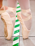 Dancers feet en pointe straddling green hazard tape