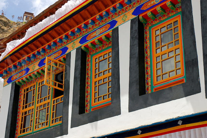 Traditional Tibetan painted windows and eaves with black surround of Drubthub Nunnery at the foot of Chagpo Ri mountain, Lhasa, Tibet, China.
