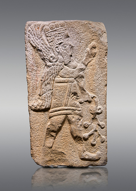 Aslantepe Hittite relief sculpted orthostat stone panel. Limestone, Aslantepe Malatya, 1200-700 B.C. Anatolian Civilisations Museum, Ankara, Turkey.<br /> <br /> Winged protective god holds a branch with fruits. in his left hand, and a fruit in his right hand.<br /> <br /> Against a gray background.