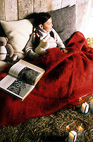 A little girl and her teddy bear are tucked up in a cosy red blanket