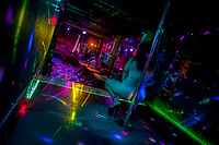 A Salvadoran sex worker performs erotic pole dance on the stage in a sex club in San Salvador, El Salvador, 13 November 2016. Sex workers' task in the club is to be an entertaining and seductive companion. Performing erotic dance on the pole they make the customers stay as long as possible and buy relatively expensive alcoholic beverages from which they have a certain share. Sex workers are not obliged to have sexual intercourse with the club customers, they decide themselves, usually according to their current economic situation.