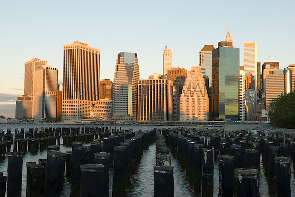 AVAILABLE FROM GETTY IMAGES FOR LICENSING.  Please go to www.gettyimages.com and search for image # 141112701.<br /> <br /> Lower Manhattan Financial District Skyline in the Early Morning Light, with Wooden Posts in the East River in the Foreground, New York City, New York State, USA