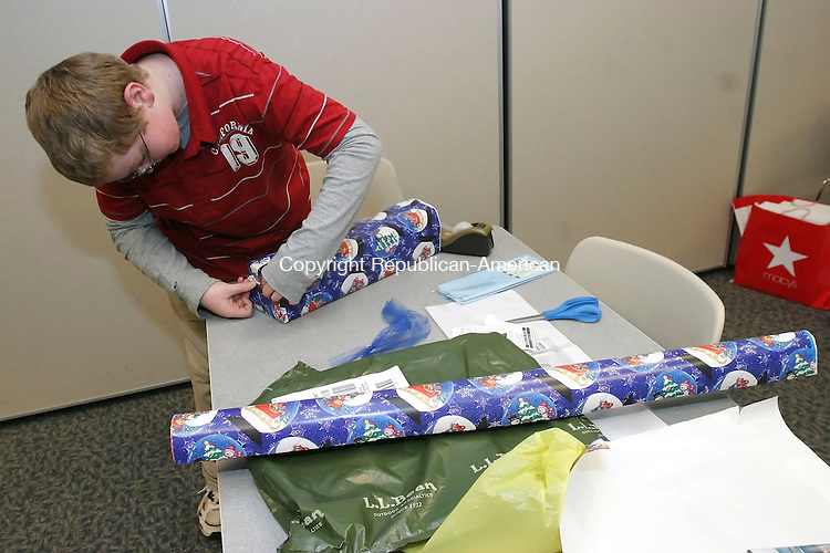 SOUTHBURY, CT 12/20/07-122007BZ02- Joe Biereder, 11, of Southbury, wraps a present as a fundraiser for the Junior Friends of the Southbury Public Library Thursday.<br /> Jamison C. Bazinet Republican-American