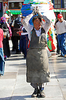 Tibetan Buddhist, wearing wooden gloves and protective leather apron,  prostrating on the Barkhor pilgrim circuit around the Jokhang Temple, Lhasa, Tibet.