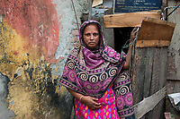 Bangladesh, Khulna. Tajila Begam works as a caretaker and cleaner for a public toilet near the busy waterway of Rupsha River in Khulna, Bangladesh. She takes (3TK to pee/ 5 to defacate) bringing in about 200 TK or $2.00 a day.The SNV Development Organization is providing fecal sludge management and occupational safety training for toilet and septic tank cleaners. In front of her home. Model released.