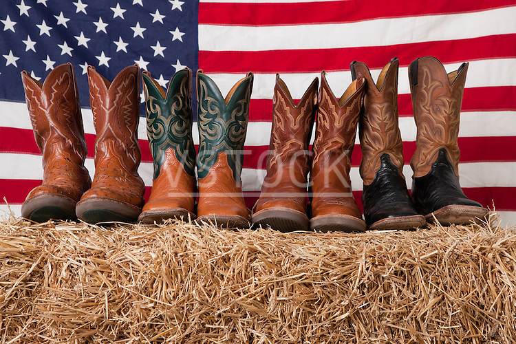 USA, Illinois, Metamora, Row of cowboy boots on haystack with American flag on background