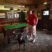 "Paulsgrove, Portsmouth, Great Britain, April 2010:.Ewems, son of the licensee is posing with his dog at ""The cross keys"" community pub in Paulsgrove near Portsmouth. Almost all guests here are the local people who know each other well and meet here everyday. .This is the last pub that remains from six that used to operate here. All others have been closed and turned into flats..(Photo by Piotr Malecki / Napo Images)..Paulsgrove, Portsmouth, Wielka Brytania, Kwiecien 2010:.Ewems, syn szefa pubu ""The cross keys"". Ten pub jest ostatnim z szesciu ktory tu dziala. Wszystkie inne zostaly zamkniete i przerobione na mieszkania..Fot: Piotr Malecki / Napo Images"