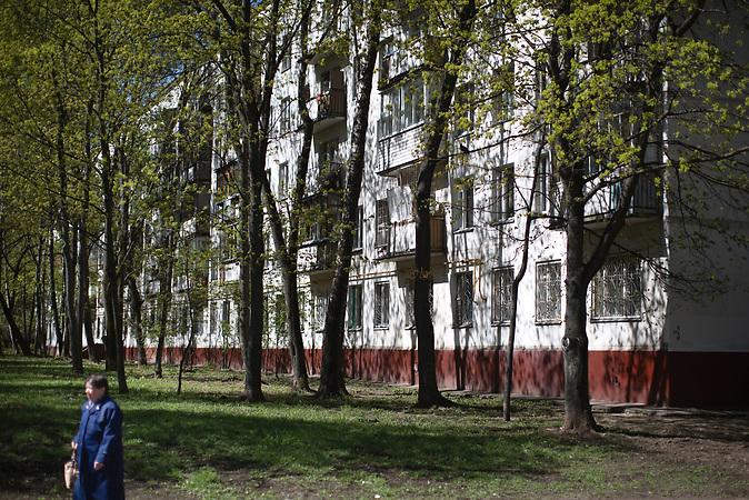 A women walks by along the 5-storage Soviet apartment blocks, so called Khrushchevka at Belyaevo district in Moscow. / Abrisspläne in Moskau 2017 für über 1 Million Menschen, Demolition plans in Moscow for over 1 Million people